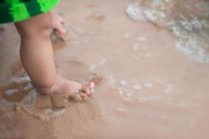 benen van een babyjongen die op het strand staat foto