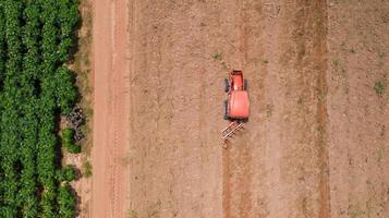 rode tractor op een landbouwgebied foto