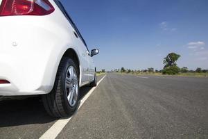 witte auto op de weg met blauwe lucht foto