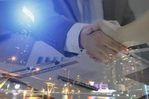 twee zakenlieden handen schudden met nachtelijke stad overlay