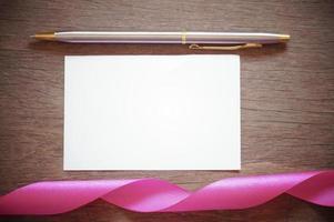 roze gekruld lint met wit papier en pen foto