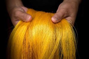 vrouwenhanden die gouden Thaise zijde tonen