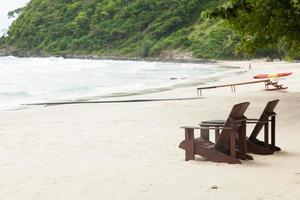houten stoelen op het strand in Thailand