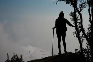 silhouet van wandelaar op de top van bergen foto