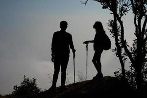 silhouet van een paar wandelaars op de top van een berg foto