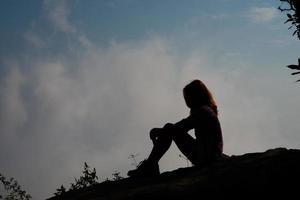 silhouet van een wandelaar zittend op de bergtop met blauwe hemelachtergrond foto