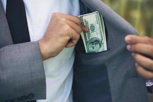 zakenman geld in zijn zak te plaatsen foto