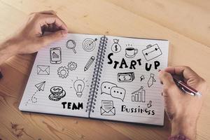 close-up van zakenman schrijven op notitieblok met doodle pictogram foto
