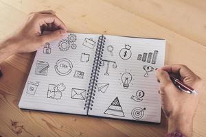 close-up van zakenman schrijven op notitieblok met doodle pictogram