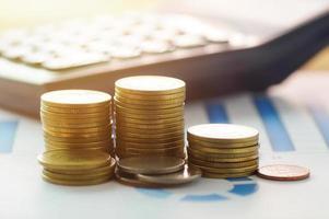 gouden munten en rekenmachine op papier grafiek