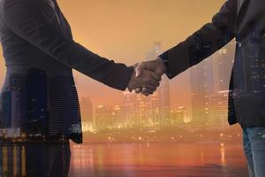 twee mensen handen schudden met stad achtergrond foto