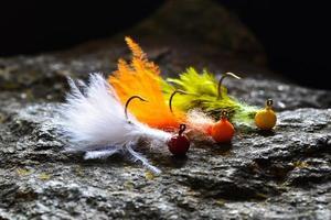 groep kleurrijke malwimpels gemaakt van veren op grijze steen foto