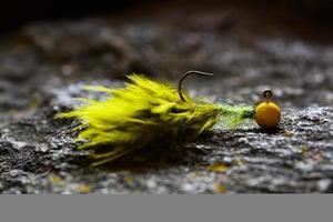 groen-gele jig-streamer maraboe gemaakt van veren op grijze steen