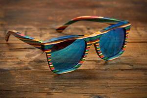 kleurrijke gestreepte houten zonnebril op houten oppervlak foto