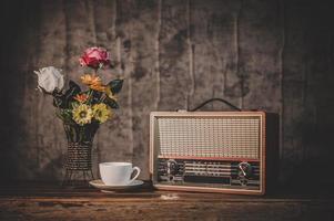 retro radio-ontvanger stilleven met koffiekopje en bloemenvazen