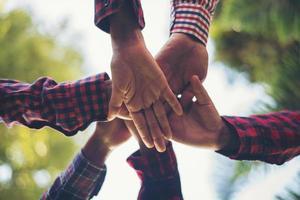 close-up beeld van jonge mensen die hun handen in elkaar zetten foto
