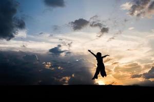 silhouet van gelukkige vrouw springen bij zonsondergang
