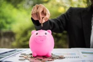 persoon munten in een spaarvarken op tafel zetten foto