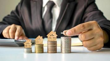 houten huismodel op munten en mensenhanden, ideeën voor investeringen in onroerend goed en financiële transacties