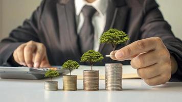 zakenmensen die bomen planten op een stapel geldbesparende ideeën en investeren in de toekomst foto