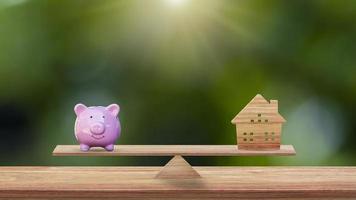 huis en varken spaarvarken op houten schalen in het park, spaarideeën voor het kopen van een nieuw huis of onroerend goed en zakelijke investeringsplanning