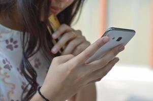 vrouw die smartphone gebruikt om online met creditcard te kopen foto