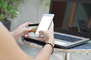 jonge vrouw die smartphone gebruikt om online met creditcard te kopen foto