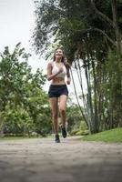 jonge sportieve vrouw die in het park loopt