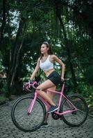 vrouw met een roze fiets foto