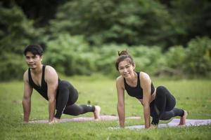 paar doet yoga in het park foto