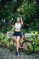 portret van een vrouw met een roze fiets in het park foto