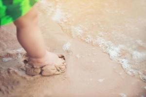 benen van een jongen die op het strand staat foto