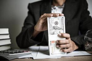 handen tellen dollar biljetten op houten tafel foto