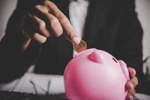 persoon munten in een spaarvarken op tafel zetten