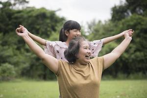 grootmoeder spelen met kleindochter buiten in het park foto