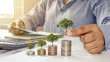 zakenman die bomen plant voor geld terwijl hij financiële boekhouddocumenten, geldbesparende ideeën en toekomstige investeringen onderzoekt