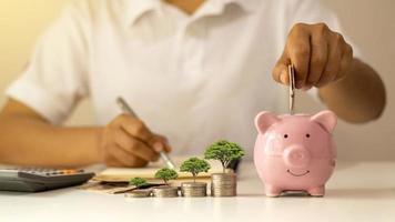 geldmunten in een spaarvarken leggen, inclusief een boom die op een stapel munten groeit, geldbesparende ideeën voor de toekomst na pensionering en winstgevend rendement op investeringen foto