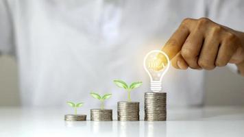 bomen groeien op munten en bollen, creativiteit op munten, ideeën voor geldgroei en bedrijfsinvesteringssystemen foto