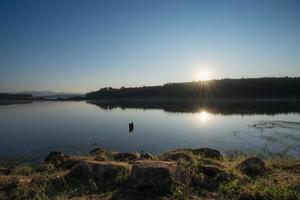 ondergaande zon op water foto
