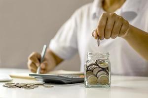 geldbesparende ideeën voor financiële boekhouding, de hand van een jonge dame stopt munten in een pot om geld te besparen foto