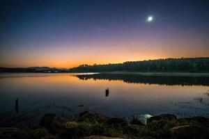 zonsondergang weerspiegeling in water foto