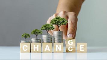 de boom op de munt en de hand draait de houten kubus om door deze te transformeren in een kans voor persoonlijke ontwikkeling en financiële groei foto