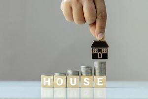 de stapels munten worden op de houten kubus gelegd met de woorden huis en de hand die het huismodel vasthoudt. financiële en investeringsideeën over vastgoedbedrijven foto