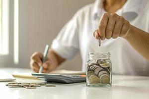 close-up van een jonge vrouw die een munt in een fles steekt, geld bespaart, een geldbesparend concept voor financiële boekhouding foto