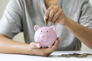 vrouwen stoppen munten in een roze spaarvarken en sparen geld om hun toekomstige pensioenfondsideeën te plannen foto