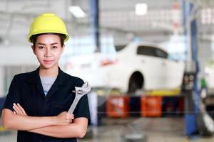 Aziatische vrouweningenieur die een moersleutel in de hand houdt