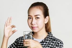 Aziatische vrouw die medicijnen gebruikt