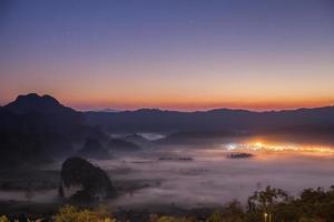 stadslichten in mist bij zonsondergang