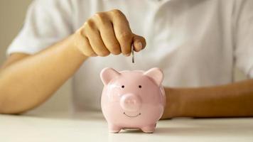vrouwen stoppen geldmunten in een spaarvarken om geld te besparen en geld te sparen voor toekomstige financiële en geldbesparende ideeën foto
