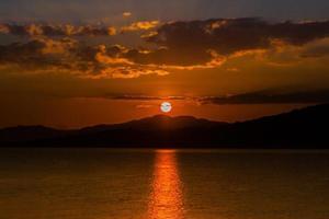 oranje zonsondergang over bergen en water foto
